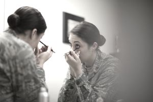 Female Soldier applying Eyeliner in MIrror