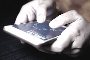 A business women checking stock charts on a mobile device. Technology and work on the go.