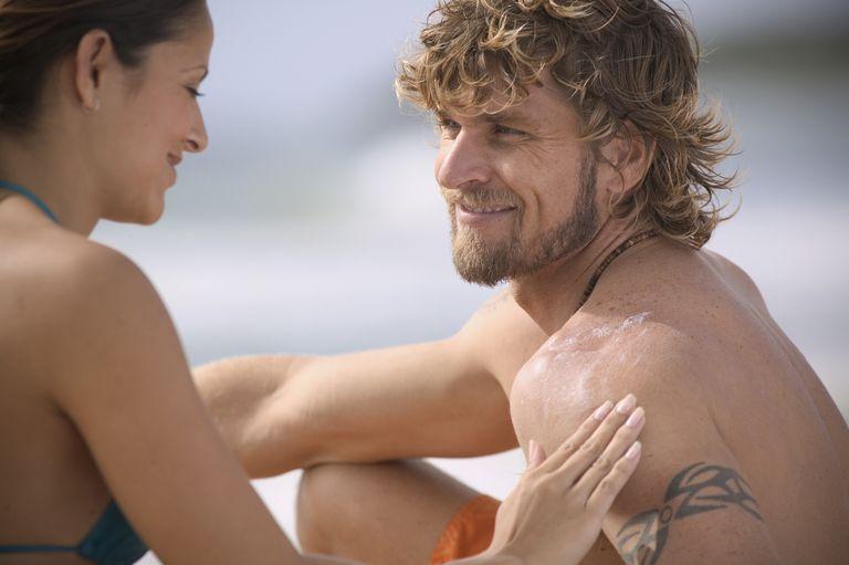 woman applying sunblock to man's tattoo
