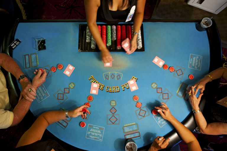 People playing three cardpoker in a casino