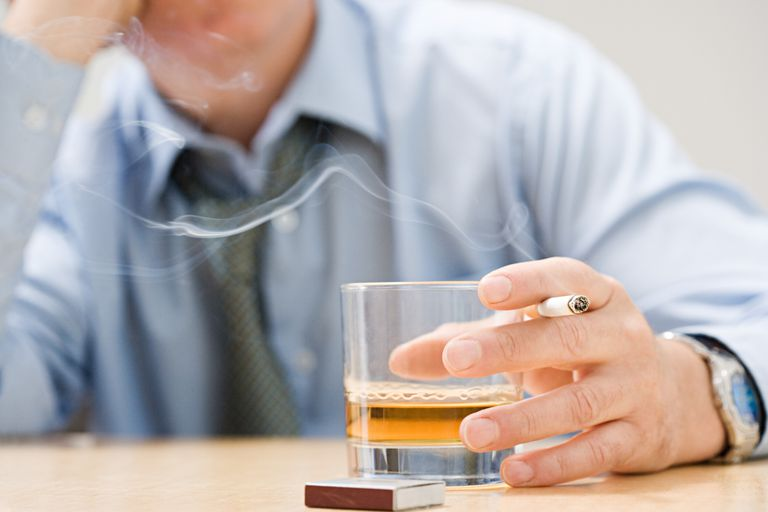 man drinking whiskey and smoking