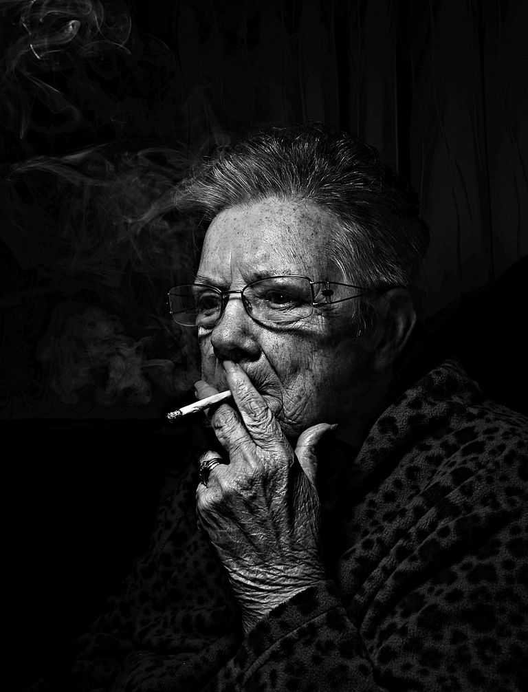 Old woman smoking a cigarette on black background