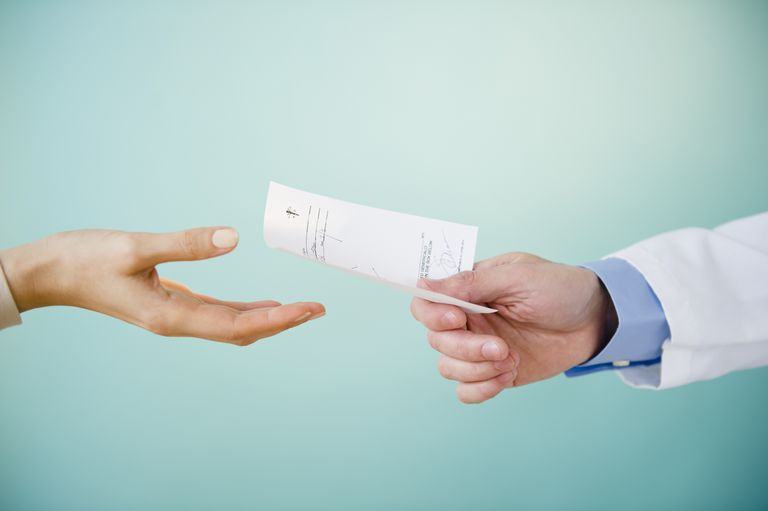 Close up of doctor's hand giving prescription to patient, studio shot