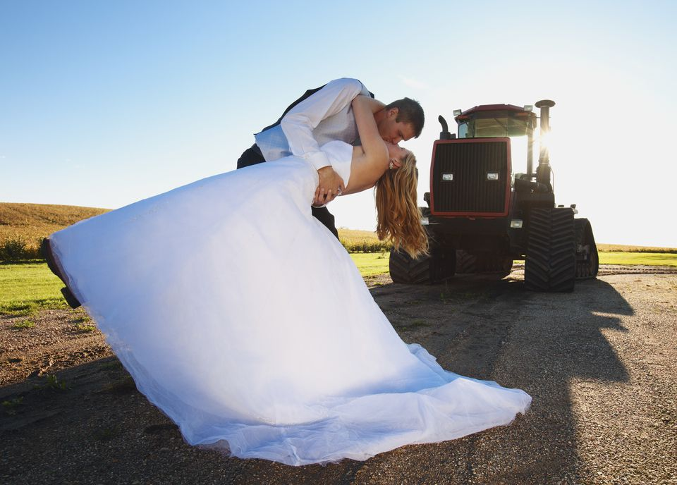 Bride And Groom Kissing In Front Of A Tractor; Pennock Minnesota United States Of America