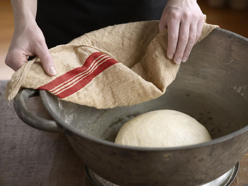 Hands covering yeast dough with a cloth (leaving it to rise)