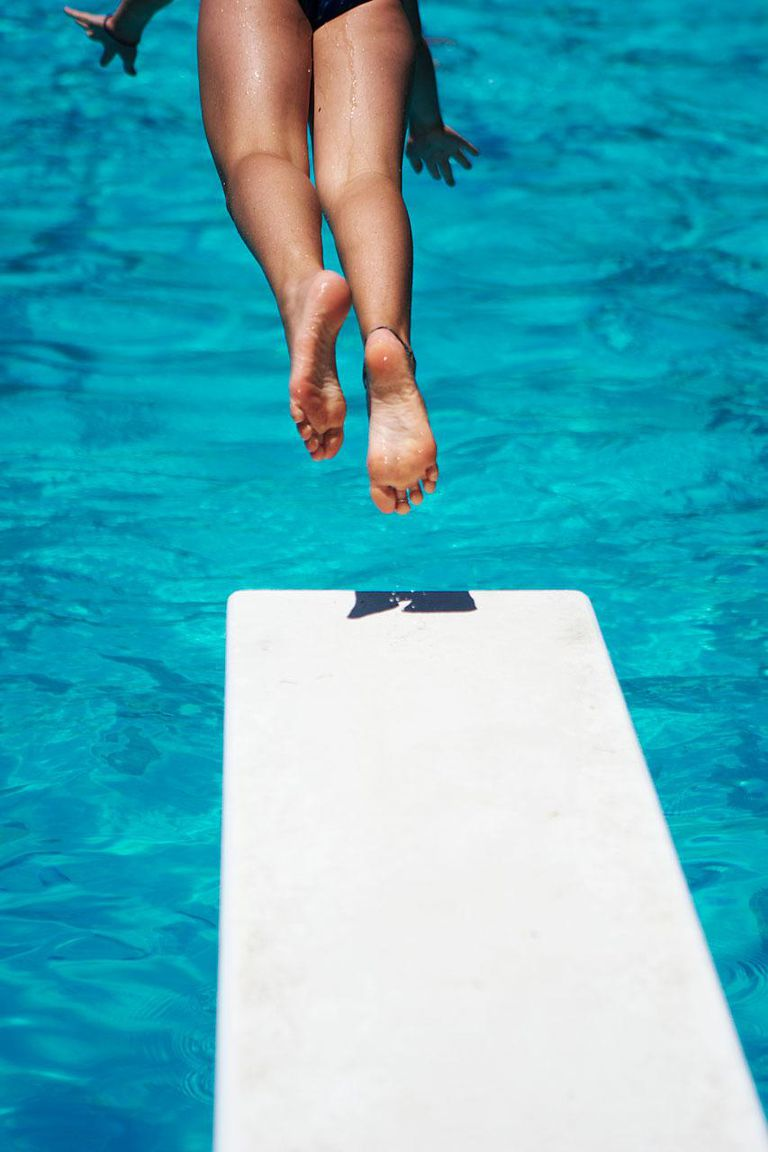 Teenage girl jumping into swimming pool from diving board