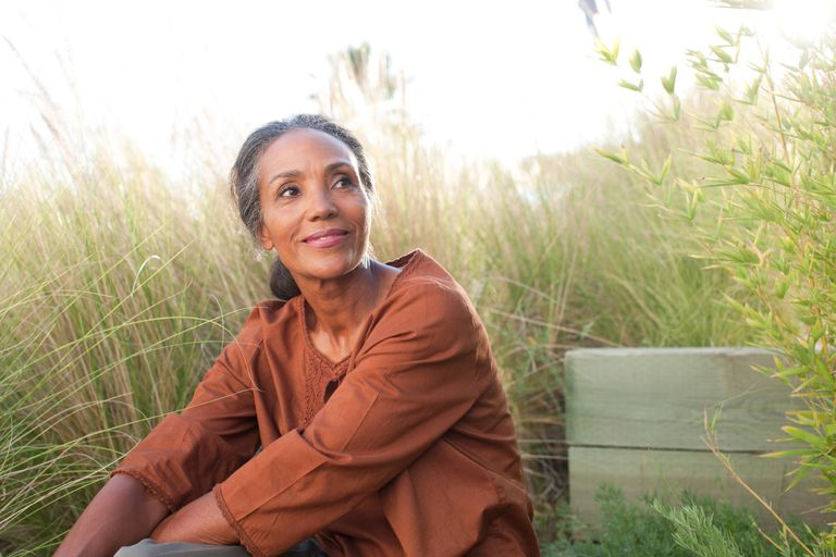 Serene woman sitting in tall grass