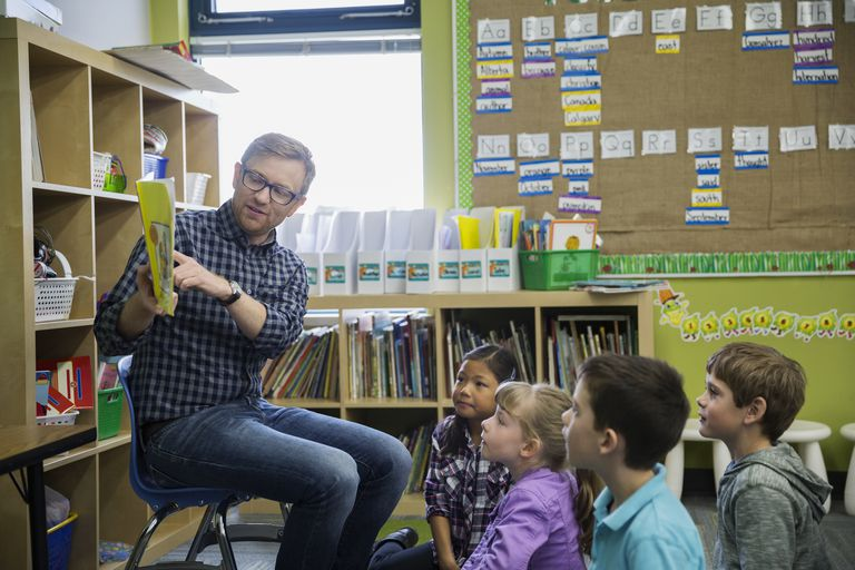 Male teacher reading to young students