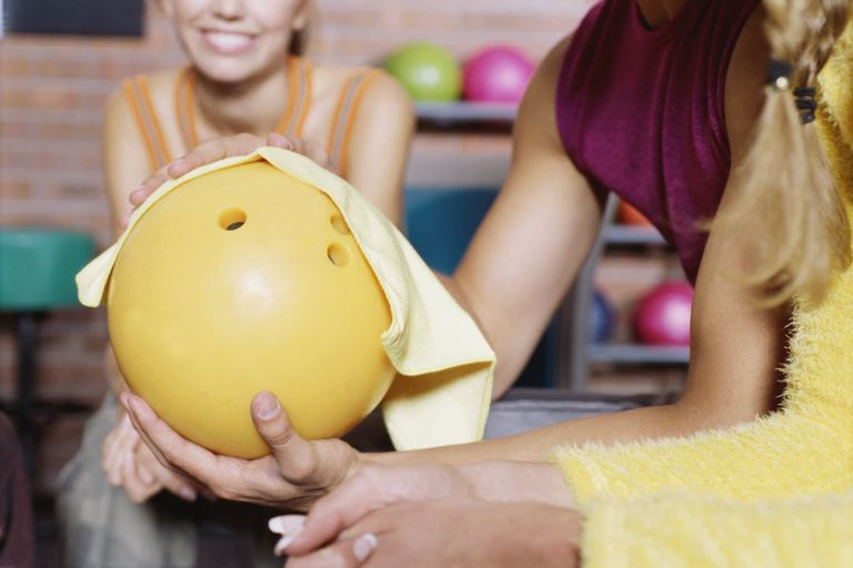 Close up of a woman polishing a bowling ball
