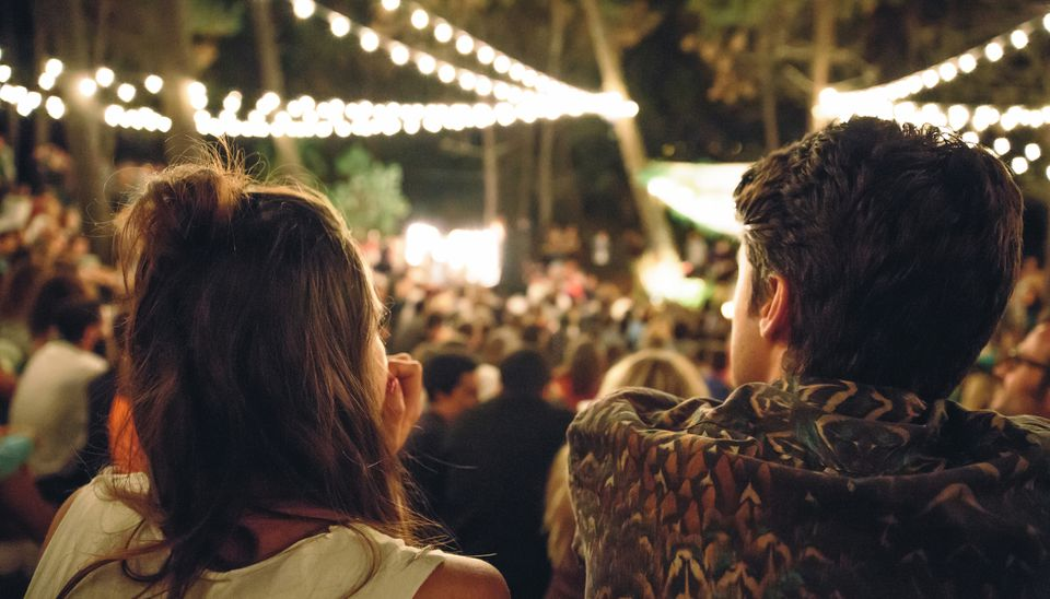 Back view of young couple sitting and enjoying in a open night music festival outdoors on summer