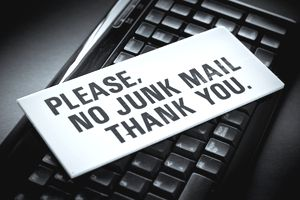 Sign about junk mail lying across a computer keyboard.