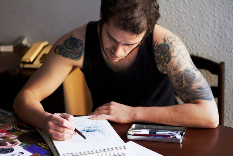 tattoo artist drawing on notepad