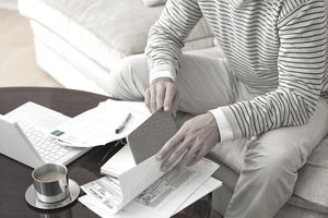 Man on sofa examining paperwork