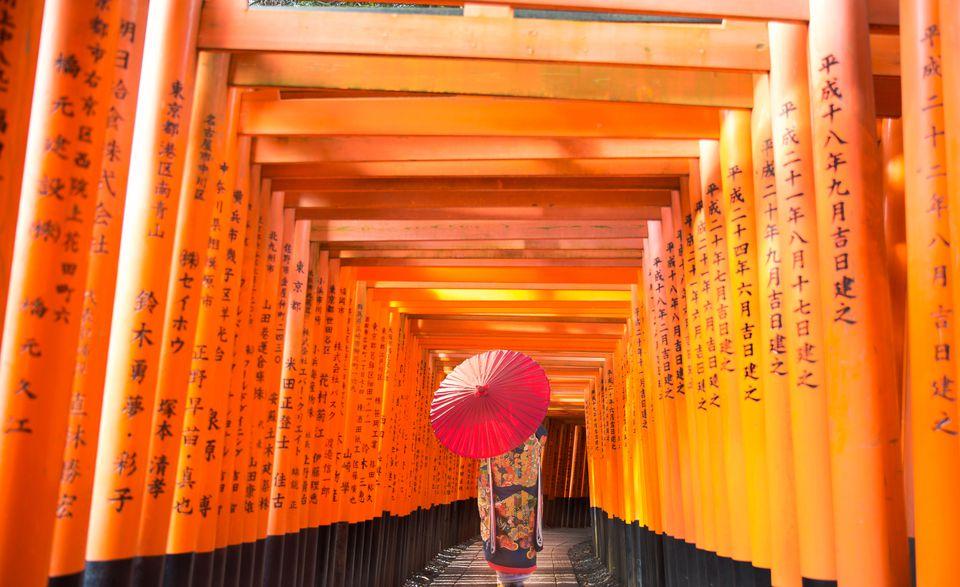 Buddhist temple. Fushimi Inari-taisha, Geisha walking through mini tori gates pathway.