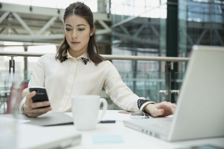 Business professional looking at smartphone and attempting to type on computer at the same time