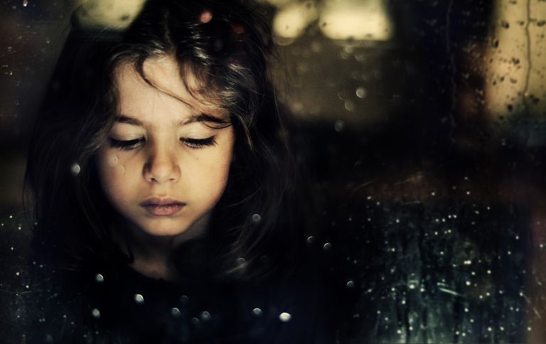 Sad girl standing behind rain covered window