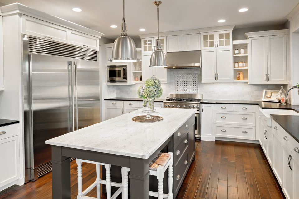White and gray kitchen with laminate wood flooring.