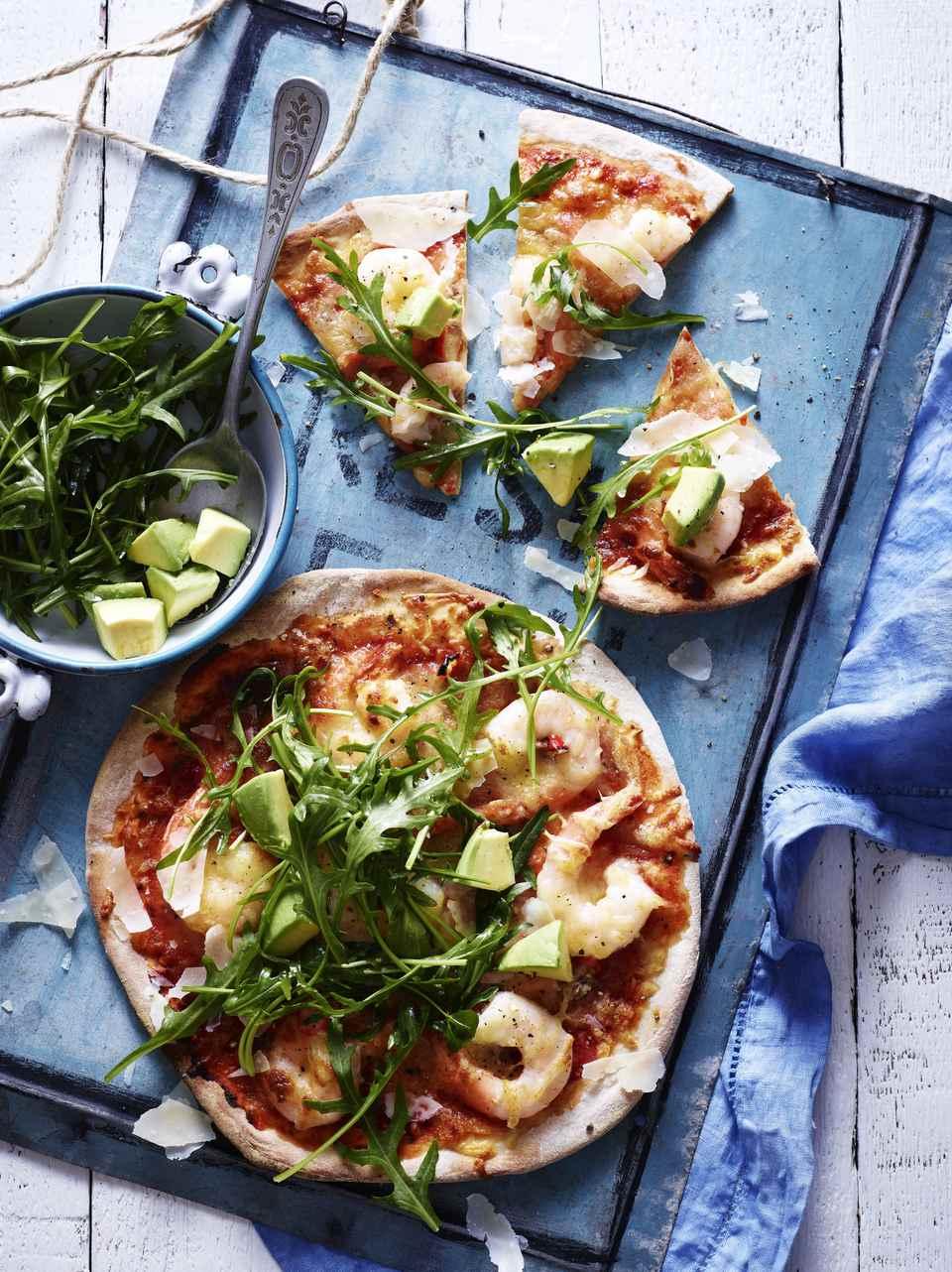 Still life of chili prawn pizza with rocket salad