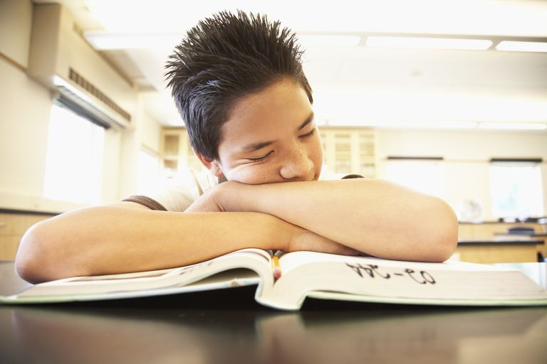 Young boy asleep on textbook