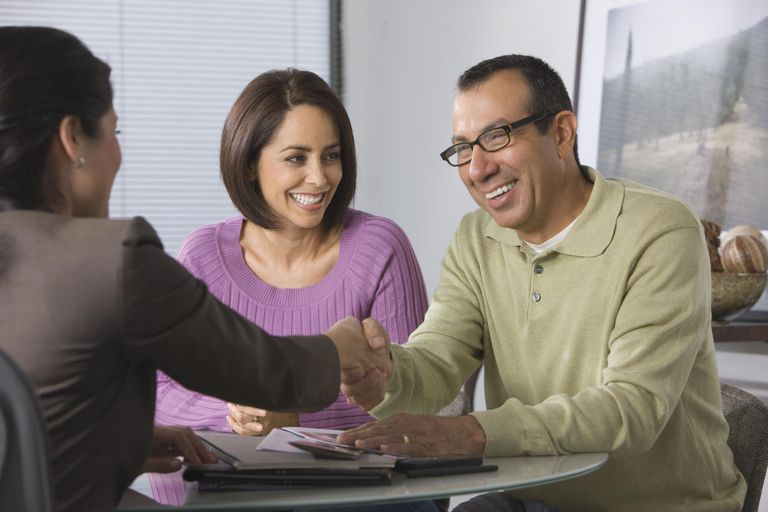 Saleswoman shaking hands with Hispanic couple