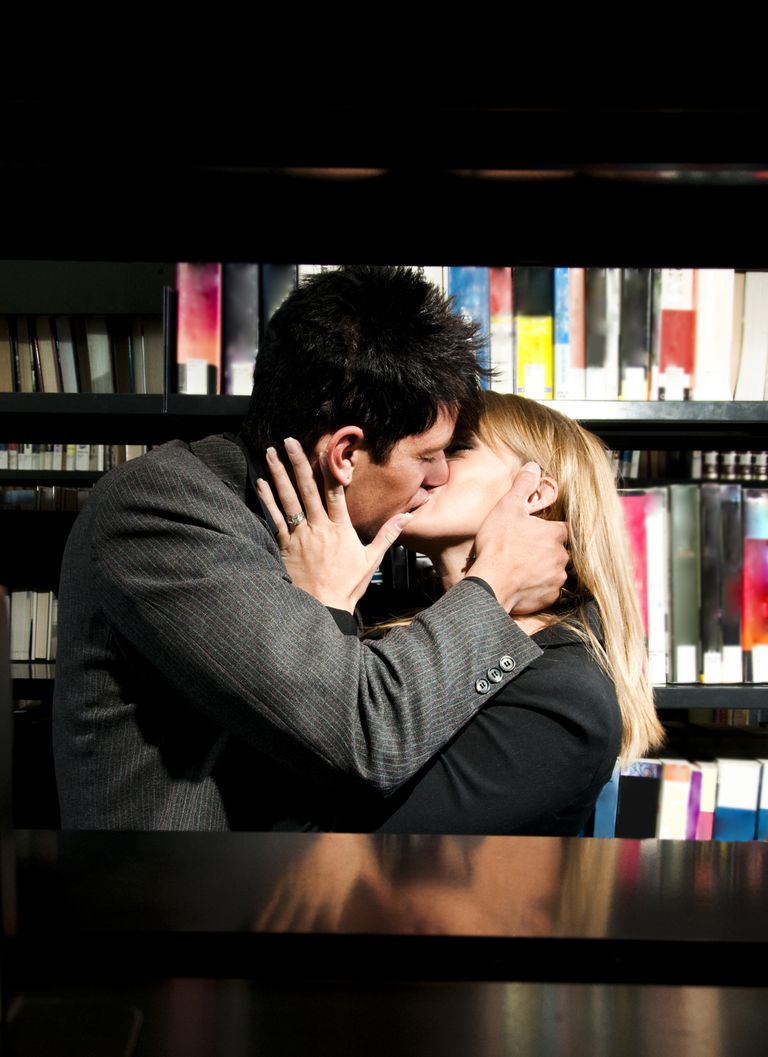Man and woman kissing in a library