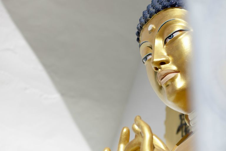 Golden statue of Buddha turning the Wheel of Dharm