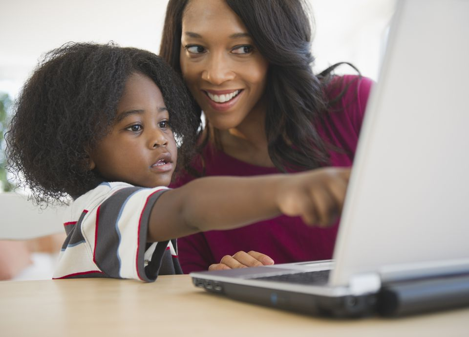 African American mother and son using laptop together