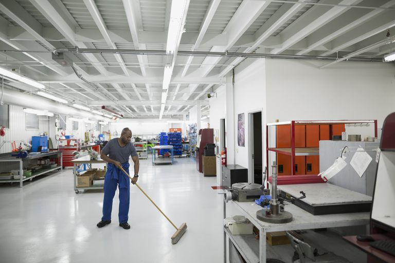 Helicopter mechanic sweeping workshop floor