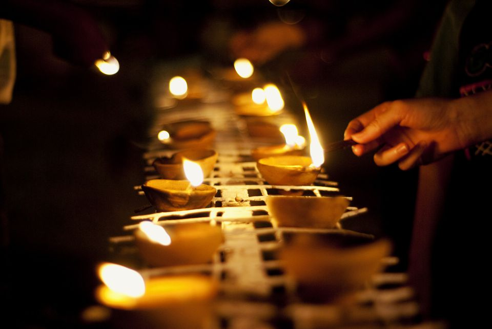A person lighting a diya