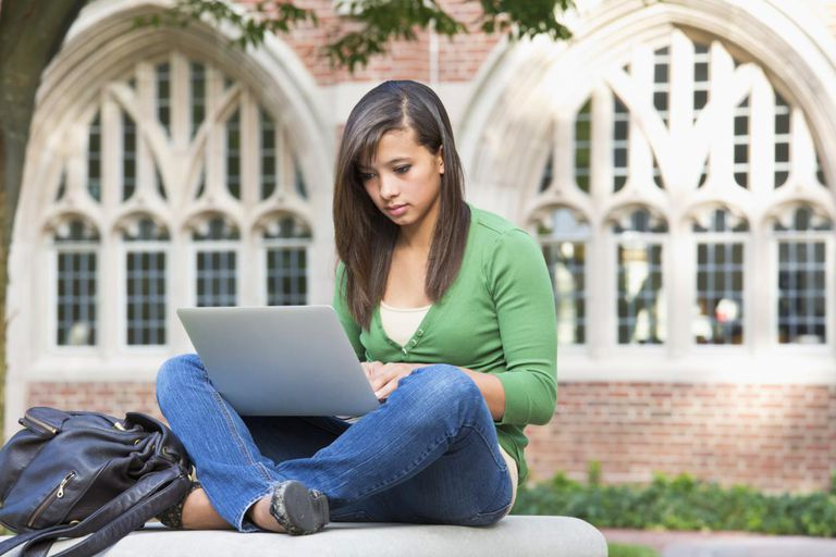 Mixed race student using laptop on campus