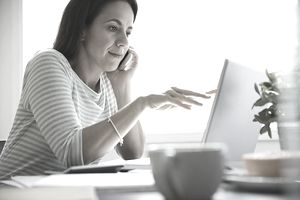 Businesswoman using technologies at desk in home office