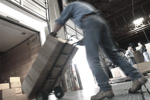 Man loading a truck with a hand truck
