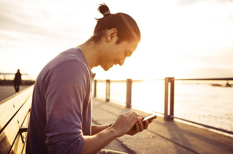 Young Man Using Smartphone In Park At Sunset