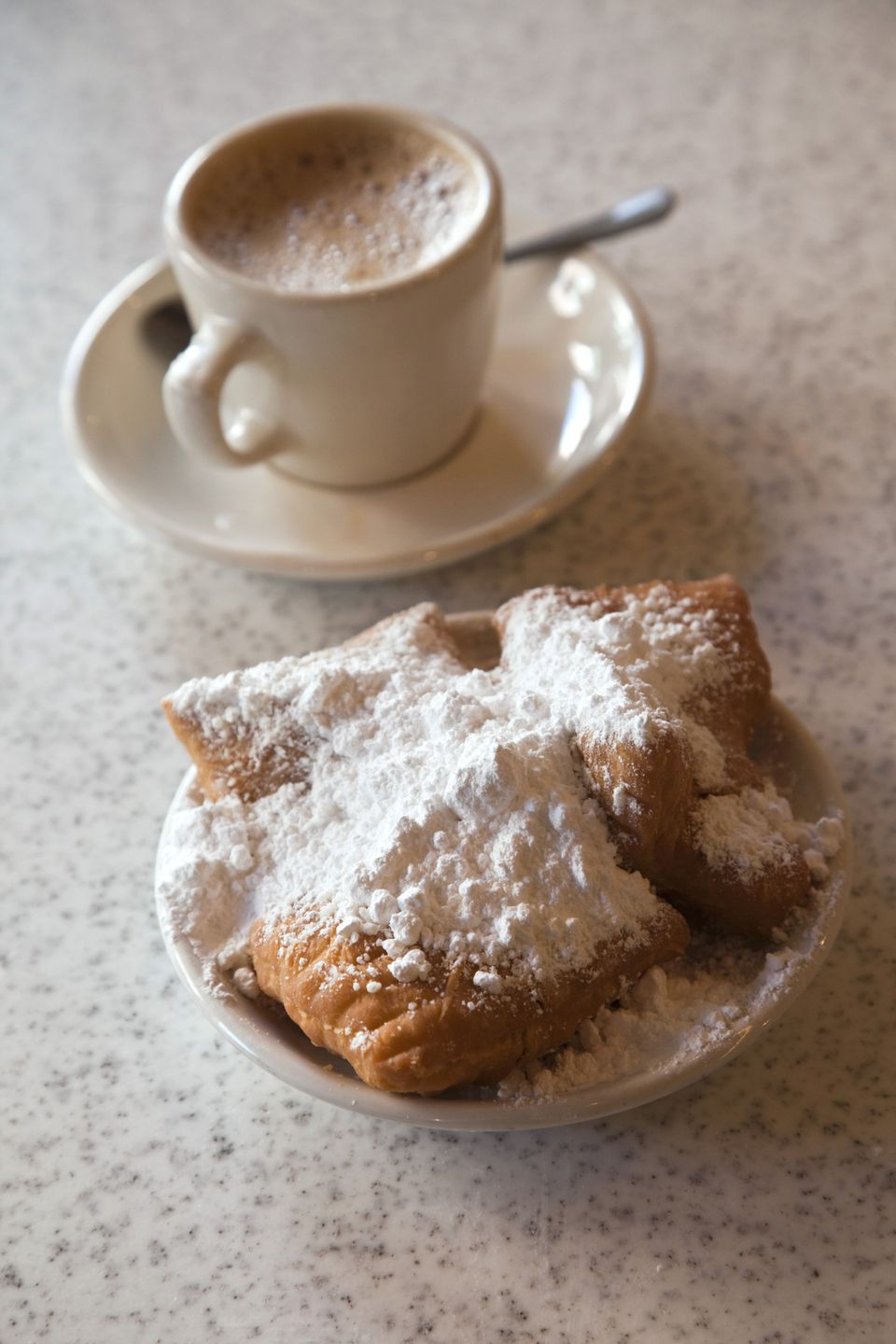 Beignets and cafe au lait at Cafe Du Monde, French Quarter, New Orleans, Louisiana, USA