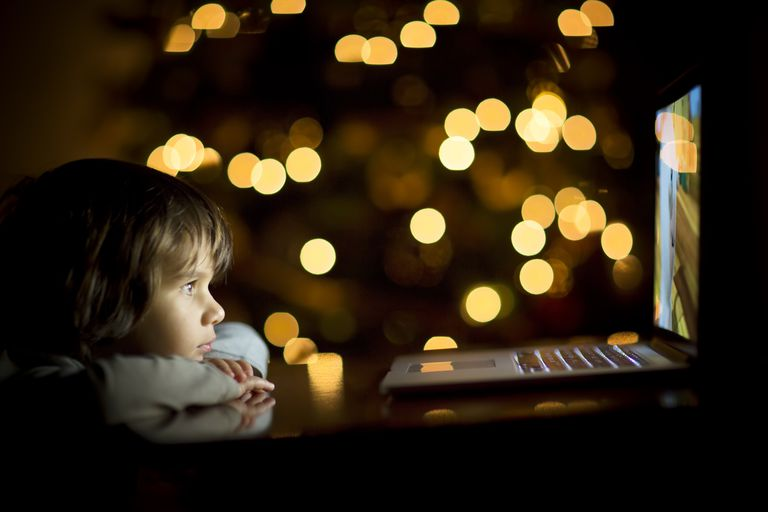 Young Boy Watching Laptop with Christmas Tree Background