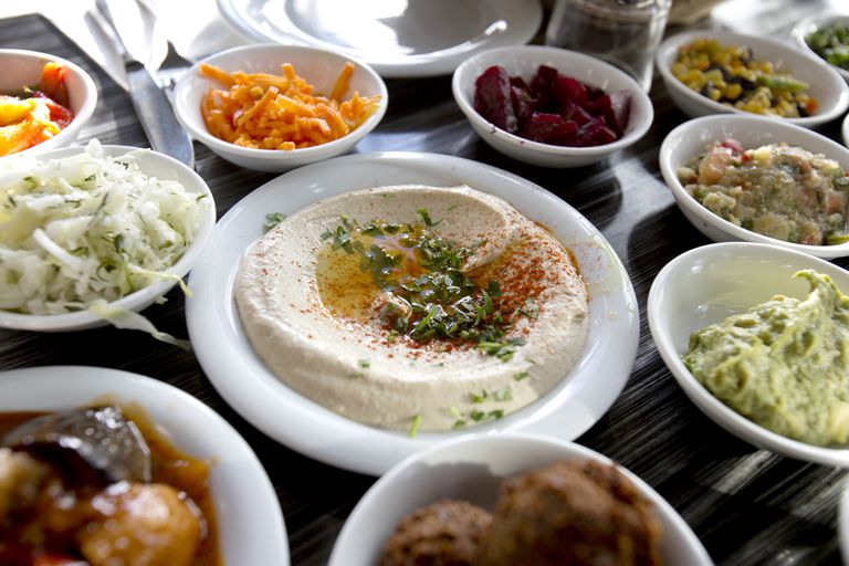 A plate of garnished hummus on table surrounded by various salads