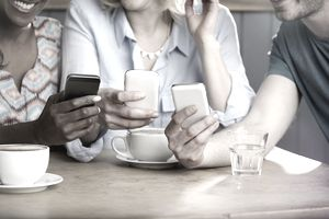 Friends comparing phones in a coffee shop