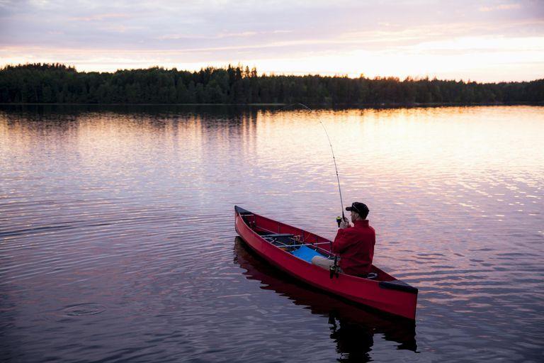 Man fishing from canoe at dusk