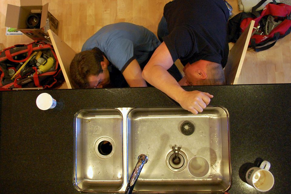 plumbers fixing kitchen garbage disposal