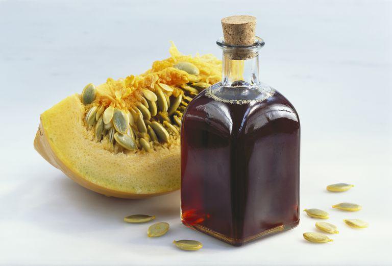 Pumpkin seed oil in bottle beside pumpkin, studio shot