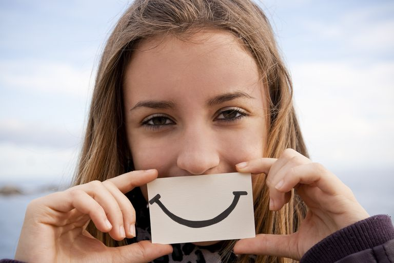 young woman smiling and holding a smiley face