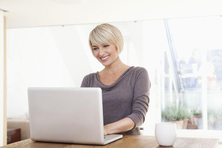 Germany, Bavaria, Munich, Woman using laptop, smiling