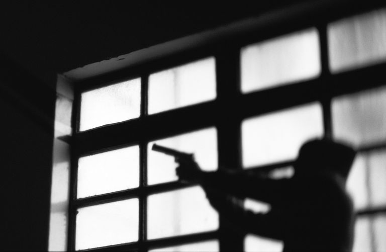 Dark silhouette of person pointing gun