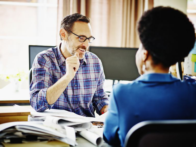 Smiling businessman and businesswoman discussing documents at workstation in accountant's office