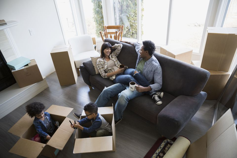 Moving boxes surrounding family relaxing in living room