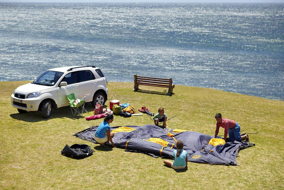 Family putting tent up by the sea