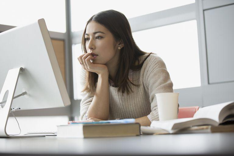 A businesswoman studies her computer screen