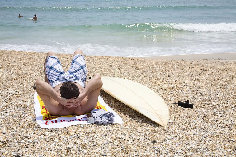 man with surf board on beach