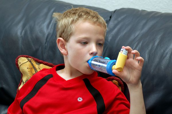 An older child using a Proventil HFA inhaler with a spacer.