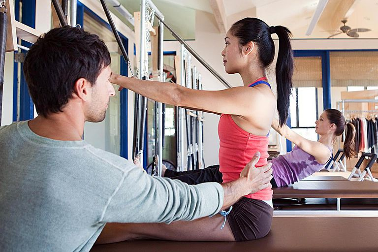 Pilates instructor assisting woman